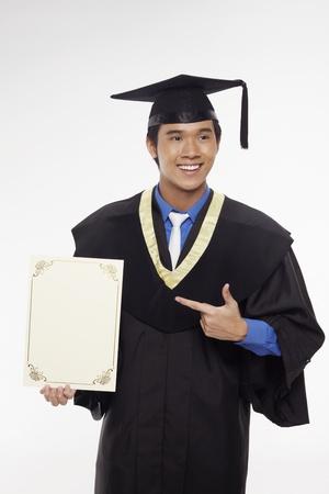 Man in graduation robe holding blank certificate Stock Photo - 17340279