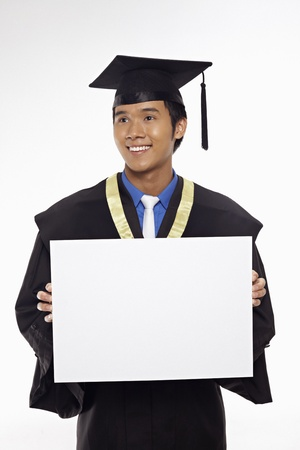 Man in graduation robe holding blank placard Stock Photo - 17340309