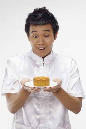 Man in traditional clothing holding mooncake on a plate Stock Photo - 17340286