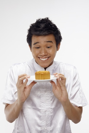 Man in traditional clothing holding mooncake on a plate Stock Photo - 17340285