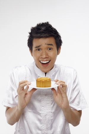 Man in traditional clothing holding mooncake on a plate Stock Photo - 17340297