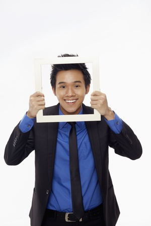 Businessman smiling and looking through cutout paper frame Stock Photo - 17340151