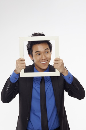 Businessman smiling and looking through cutout paper frame Stock Photo - 17340262