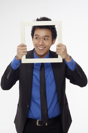 Businessman smiling and looking through cutout paper frame Stock Photo - 17340267