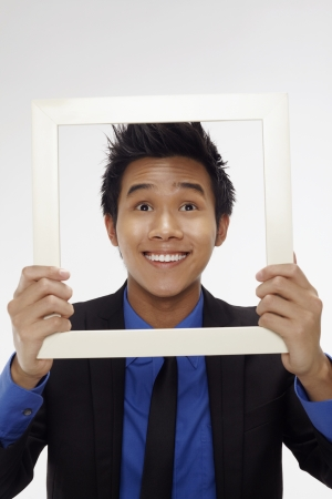 Businessman smiling and looking through cutout paper frame Stock Photo - 17340288