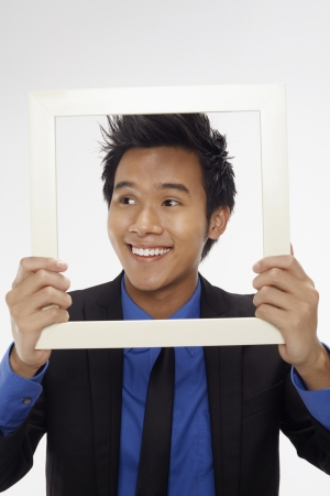 Businessman smiling and looking through cutout paper frame photo