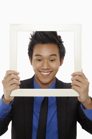 Businessman smiling and looking through cutout paper frame Stock Photo - 17340152