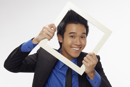 Businessman smiling and looking through cutout paper frame Stock Photo - 17340259
