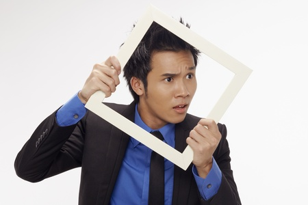 Puzzled businessman looking through cutout paper frame Stock Photo - 17340233