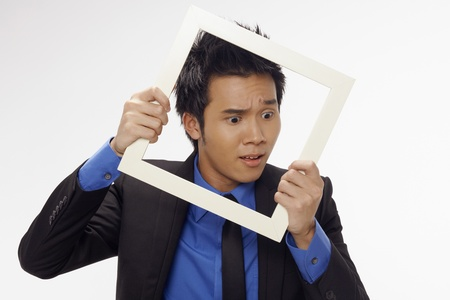 Puzzled businessman looking through cutout paper frame Stock Photo - 17340268