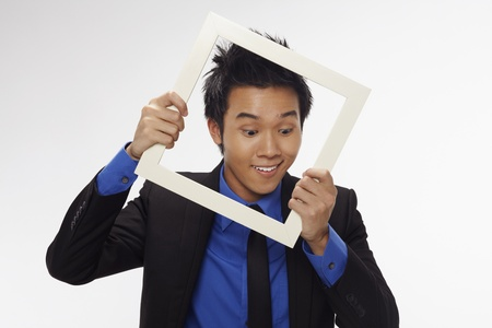 Businessman smiling and looking through cutout paper frame Stock Photo - 17340231