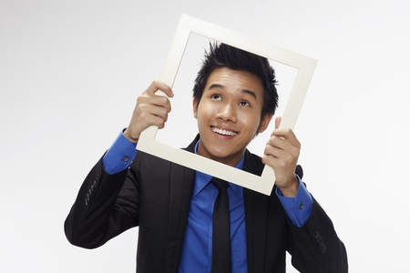 Businessman smiling and looking through cutout paper frame Stock Photo - 17340227
