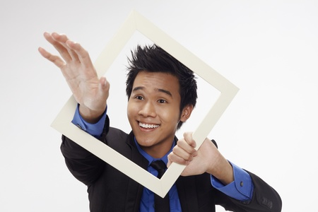 Businessman smiling and reaching out through cutout paper frame Stock Photo - 17340212