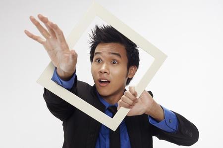 Businessman reaching out through cutout paper frame Stock Photo - 17340219