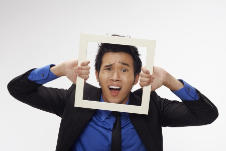 Stressed businessman looking through cutout paper frame Stock Photo - 17340254