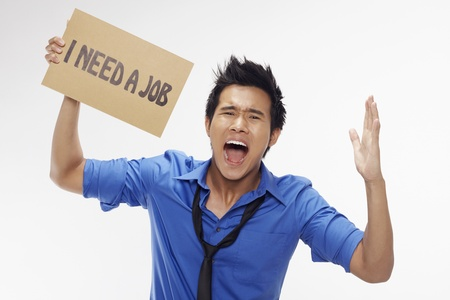 demotivated: Businessman holding  I need a job  sign