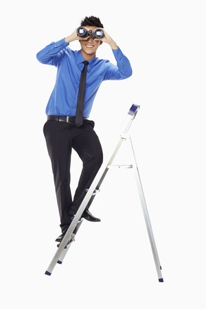 Businessman on ladder looking through binoculars photo