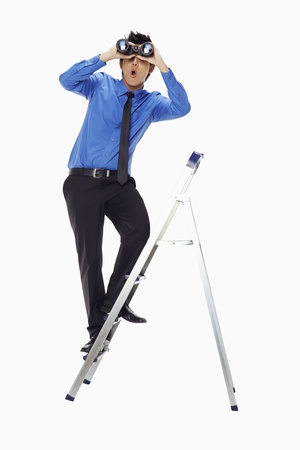 Businessman on ladder looking through binoculars Stock Photo - 17339806