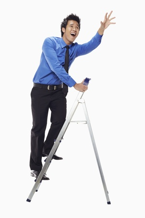 Businessman on ladder with his arms reaching out Stock Photo - 17339811