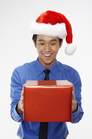 Businessman wearing Santa hat and holding a gift box Stock Photo - 17340269