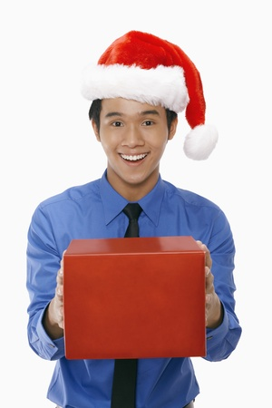 Businessman wearing Santa hat and holding a gift box photo