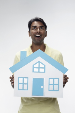 30 34 years: Man holding a cutout of a house