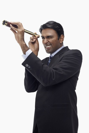 Businessman looking through telescope photo