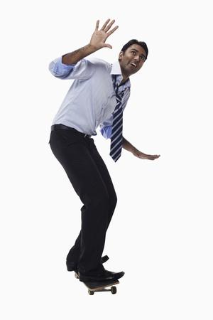 startled: Businessman standing on skateboard