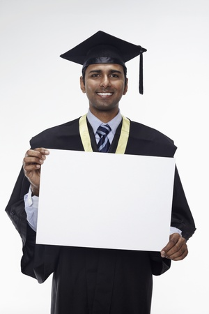 Man in graduation robe holding blank placard photo