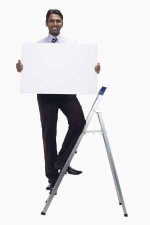 Businessman on ladder holding blank placard photo