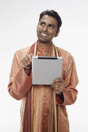 30 34 years: Man in traditional clothing using digital tablet
