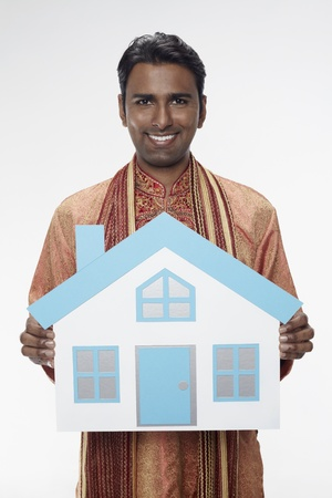 30 34 years: Man in traditional clothing holding a cutout house