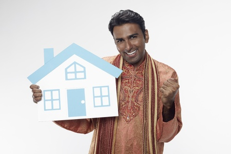 Man in traditional clothing holding a cutout house  photo