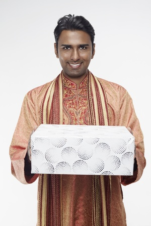 Man in traditional clothing holding gift box photo