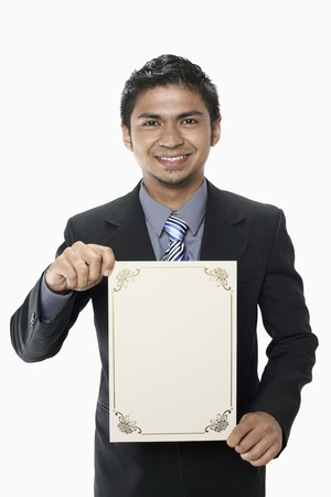 Businessman holding a blank certificate Stock Photo - 17962533