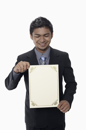Businessman holding a blank certificate Stock Photo - 17962528