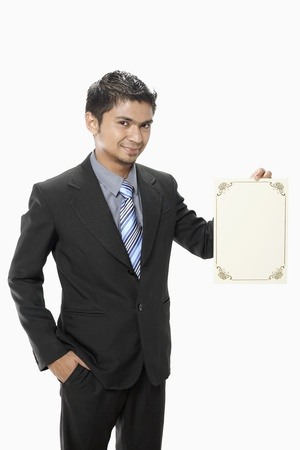 Businessman holding a blank certificate photo