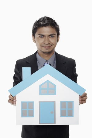 Businessman holding a cutout house photo