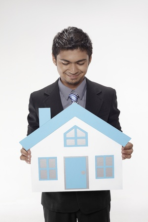 Businessman holding a cutout house Stock Photo - 17962536
