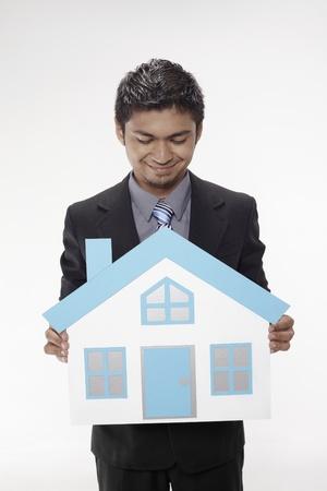 Businessman holding a cutout house Stock Photo - 17962536