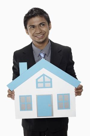 Businessman holding a cutout house Stock Photo - 17962532