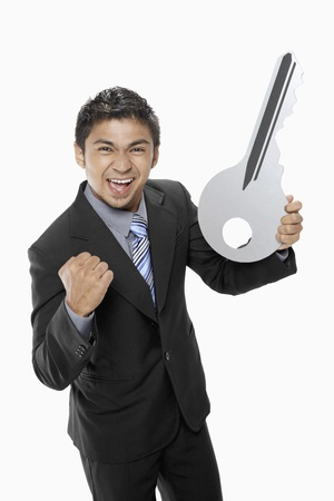 side keys: Businessman holding a big key Stock Photo