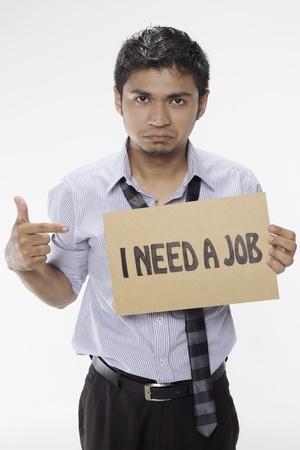 Businessman holding  I need a job  sign Stock Photo - 17961941