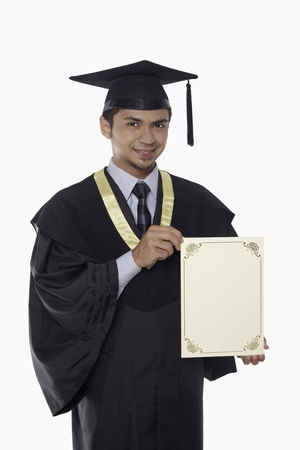 Man in graduation robe holding a blank certificate photo