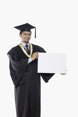 Man in graduation robe holding a blank placard photo