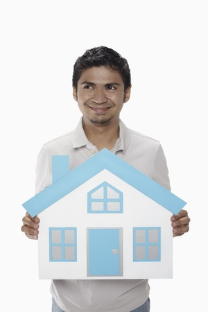 Man holding a cutout house photo
