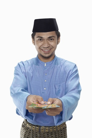 Man in traditional clothing presenting green packets photo