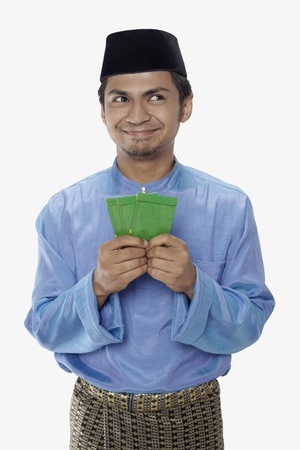 Man in traditional clothing holding green packets Stock Photo