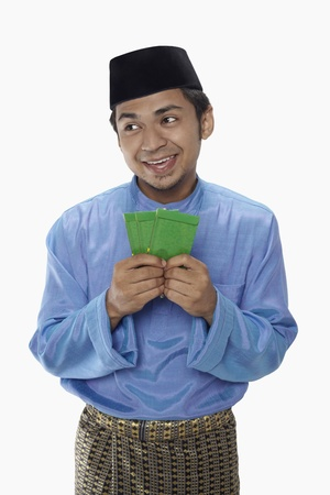 Man in traditional clothing holding green packets photo