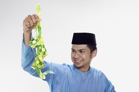 Man in traditional clothing holding ketupat photo